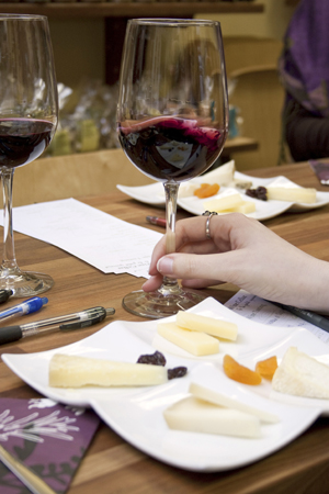 A glass of wine and a plate of cheese at a tasting