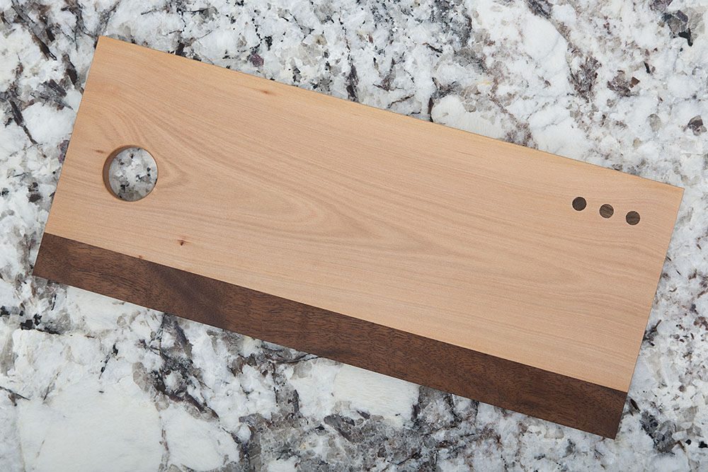 Bug dammage was exposed during the milling process of this cheeseboard, which was easily amended with a strip of walnut.