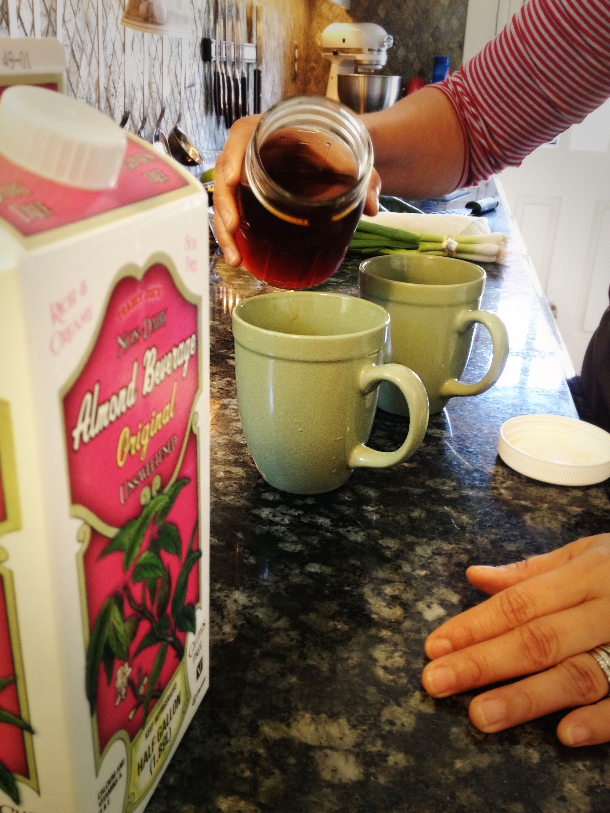 Sandra pours concentrated rooibus (an herb) into our chai tea.