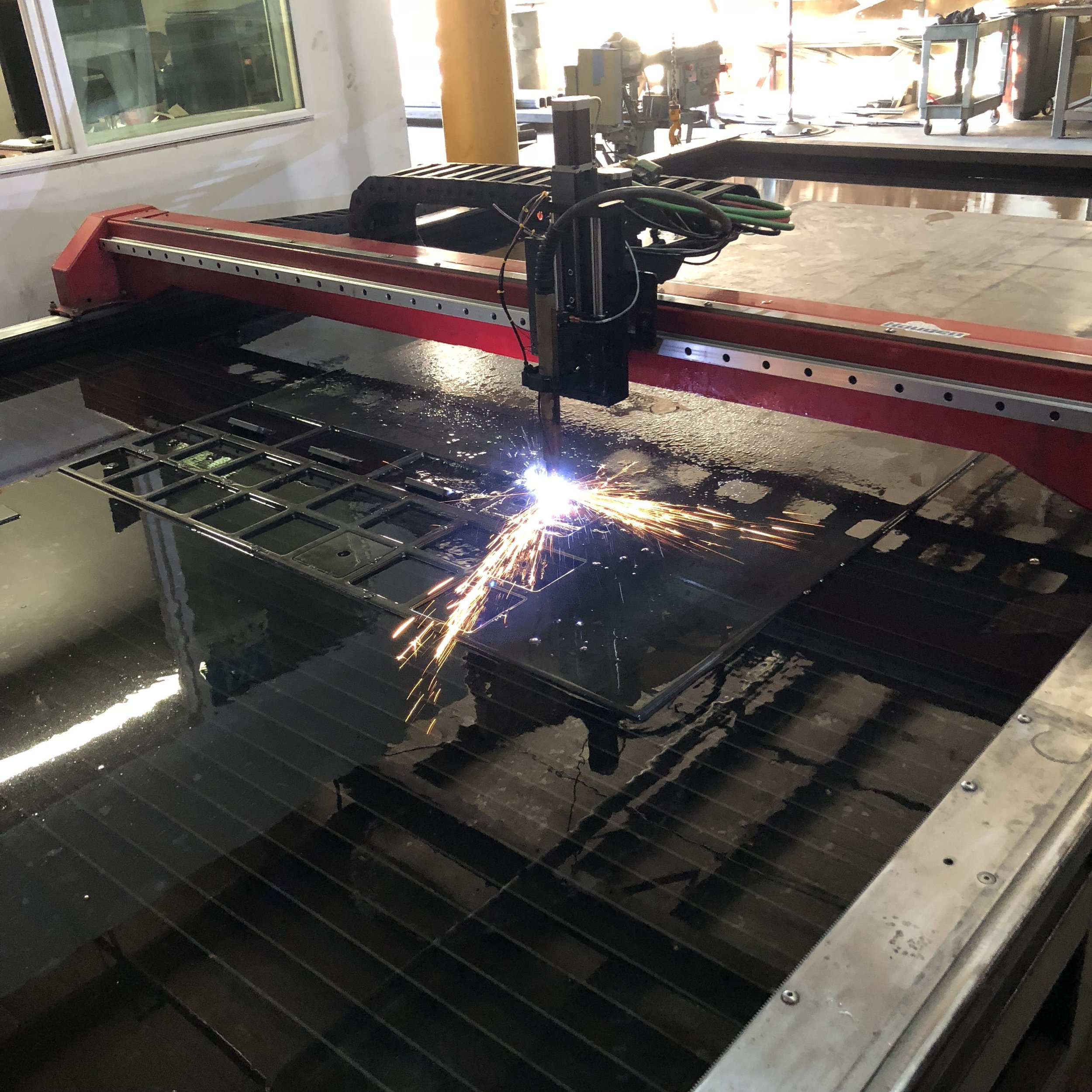 "CNC Plasma Cutting 1/2"" Plate (submerged in water) for mounting flanges."