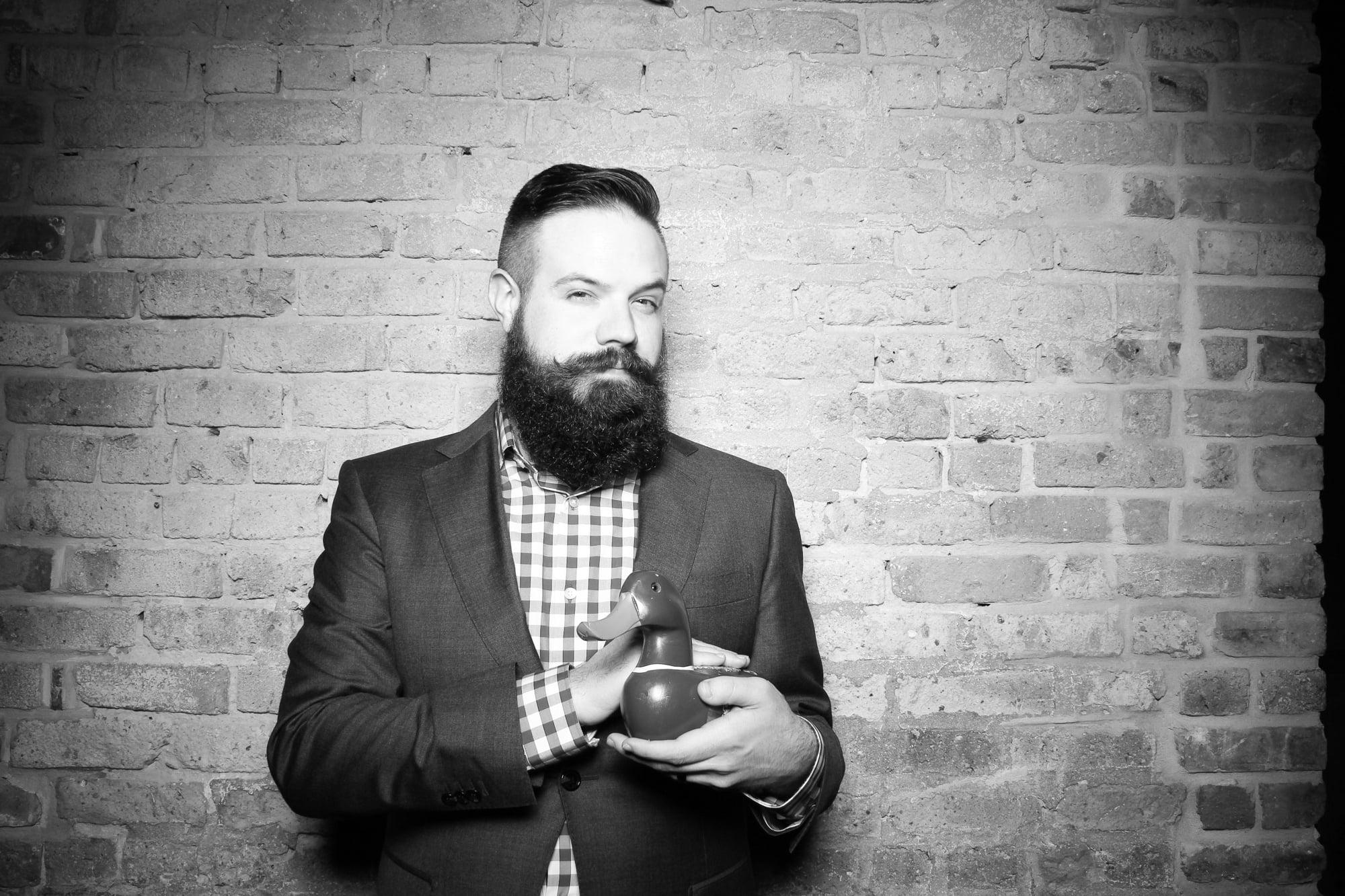 Bearded man holding wooden duck. Digital photograph ca. 2016.