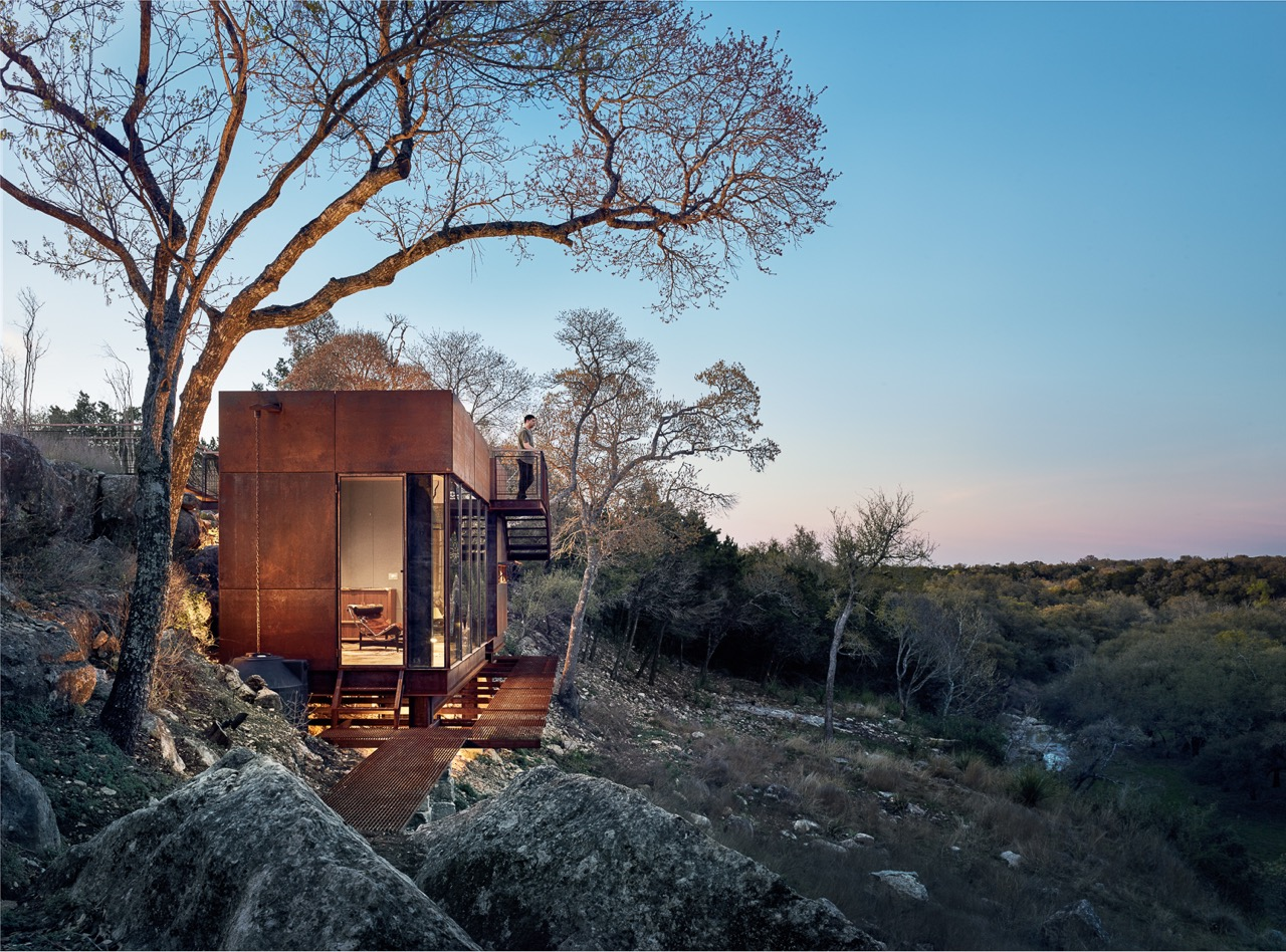 """CLEAR ROCK RANCH     2019 TXA Design Award Winner      2017 AIA Austin Design Award Winner      Clear Rock Lookout is a raw steel hunting blind, writing studio, and observation deck that celebrates the stunning landscape and wildlife views. The 450sf building is nestled below a limestone cliff edge, and has to be """"discovered"""" when approached from the top of the mesa. This gradual reveal of the building strengthens the unfolding landscape panorama made possible from the unique vantage provided by the structure.  The site was specifically chosen for its views by the owner after years of slowly traversing and mapping the wooded cliff edge. The modern form contrasts with the Hill Country vernacular used on the rest of the 1,000 acre West Texas ranch. Naturally weathering steel was chosen to age with the surroundings and to pay homage to the owner's youth spent welding oil tanks.  Large sheets of glass, a variety of warm woods, and a highly detailed assembly complete the """"jewelbox in the landscape"""" expression of the lookout.   Contractor:  Ron Reue Construction   Steel Fabrication :  Longhorn Welding    Structural Engineers :  Arch Consulting Engineers    Photo Credits :  Casey Dunn    Publications:   Texas Made/Texas Modern ,  Dezeen  ,  ArchDaily ,  Dwell  ,  Uncrate ,  Texas Architect Magazine ,  Austin Home Magazine"""