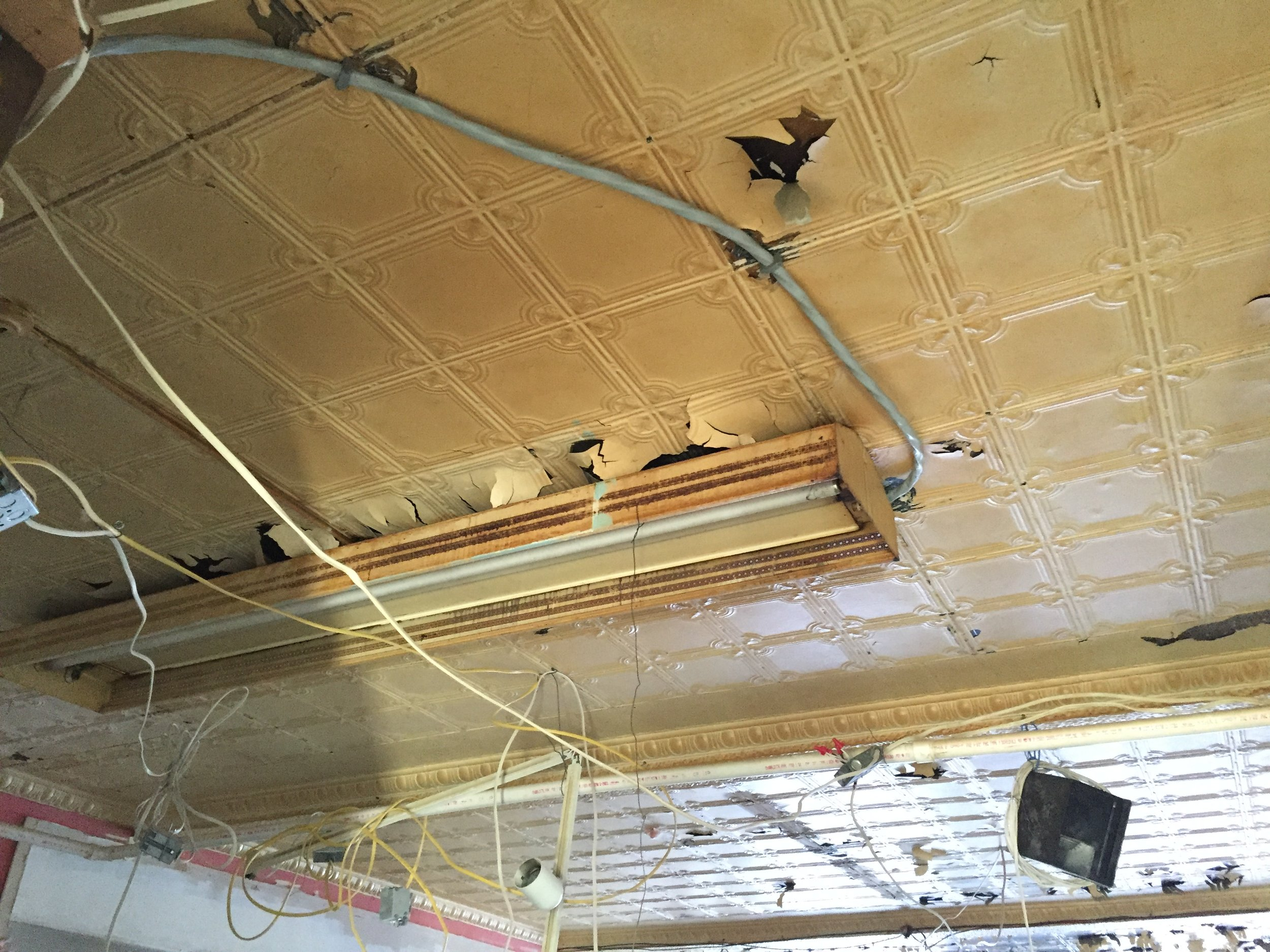 Before:  Peeling tin ceiling surrounded by spaghetti wires and random pipes...yikes!