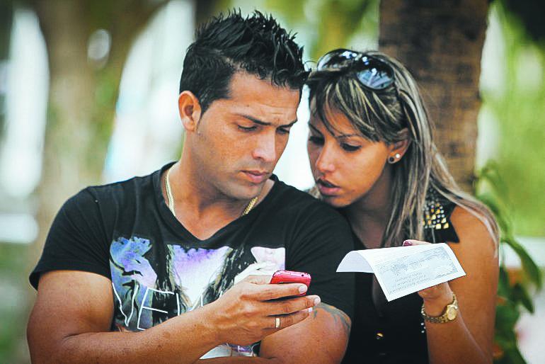Dos cubanos se conectan a internet desde un teléfono móvil.