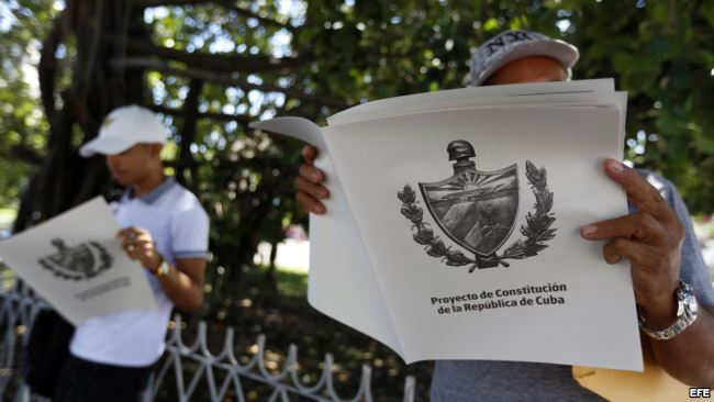Dos personas leen el Proyecto de Constitución de la República de Cuba