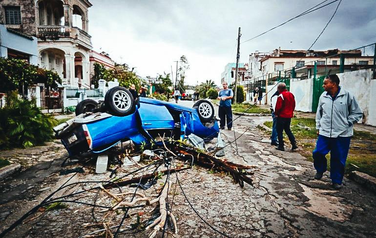 Vecinos observan un auto volcado por un tornado en la madrugada de este lunes, en La Habana. EFE