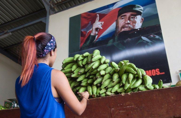 Una mujer es vista en un agromercado en el que se observa una foto del fallecido dictador Fidel Castro en La Habana, Cuba. EFE/Yander Zamora