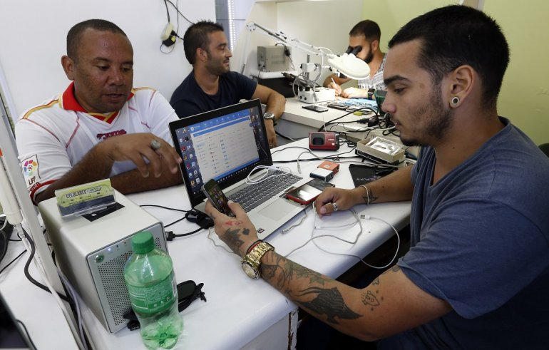 Dos personas acuden a un negocio privado de reparación de teléfonos celulares en La Habana, Cuba. EFE / ARCHIVO