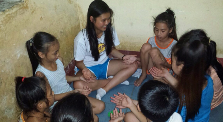 The children in the community and I play a game together.