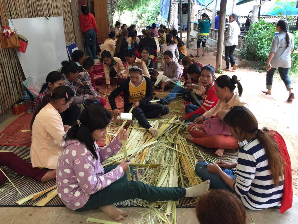 Girls learning weaving skills.