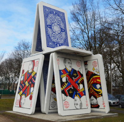 """THE DECLINE / 2016   The """"Decline"""" is a 60-ton construction shows a house of cards made of nine concrete play cards and has a scale of thirty five feet high and nineteen and a half feet wide. The construction is literally as big as a house. The traditional images on the cards are replaced by a selection of historical figures, world leaders and dictators. The selected images and the shape of the cards are being presented as a metaphor    Read more"""