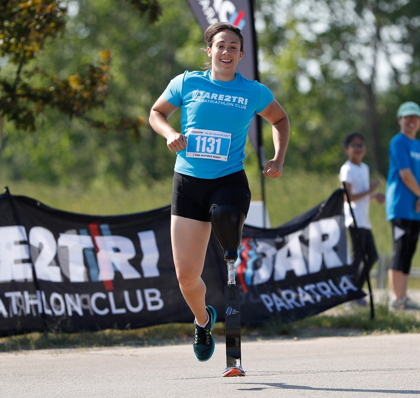 Female amputee athlete racing to the finish line.