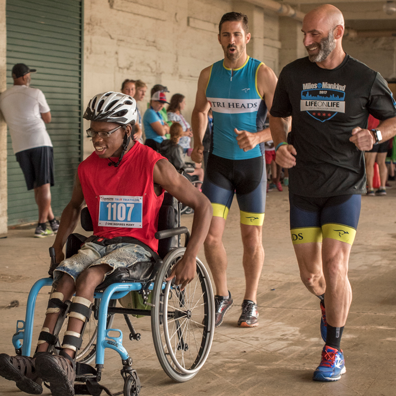 Dare2tri volunteers running alongside youth in wheelchair.