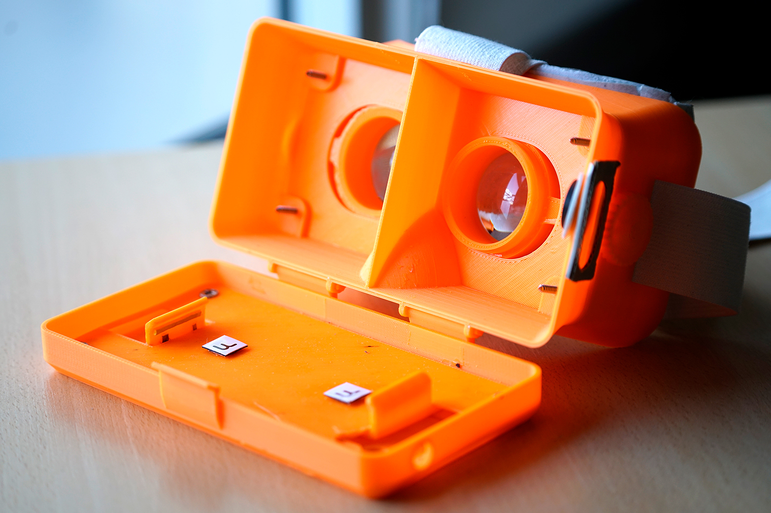 Abierto. Se ven las lentes con dioptría ajustable y el sostén del smartphone.