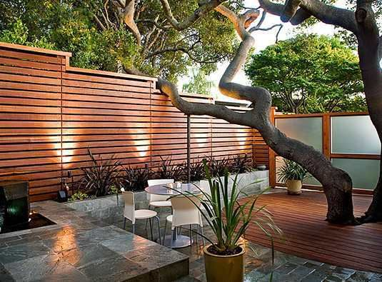 This eye catching wood fence is a great example of an easy way to incorporate wood into your backyard room. This backyard room took the inclusion of this element a step further by adding wood on the ground and wood accents around the windows.  Image of wood feature courtesy of re-nest.com