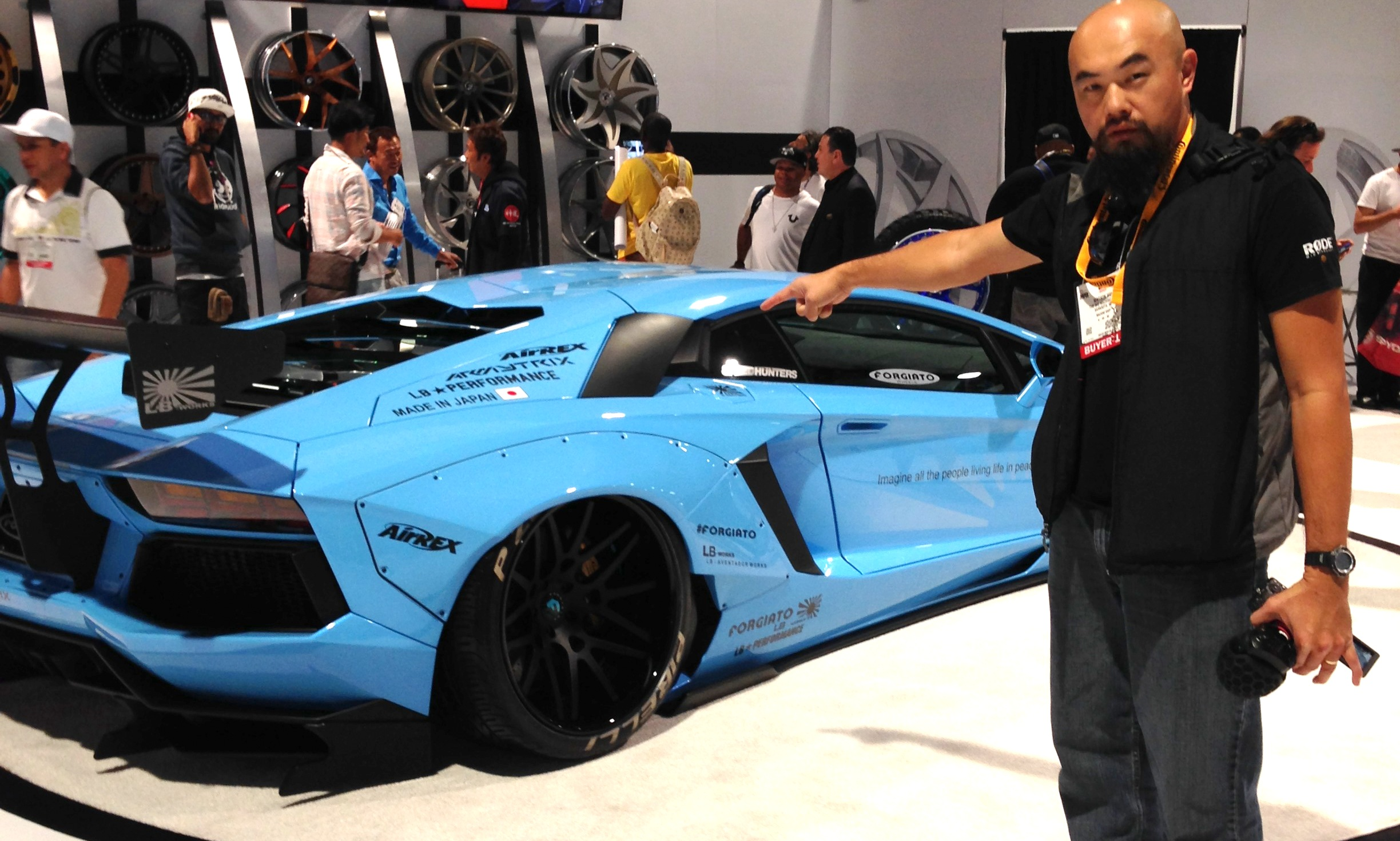 Watson Wu holding the  RØDE   SVM X mic,  posing with a Liberty Walk Lamborghini at the SEMA Show.