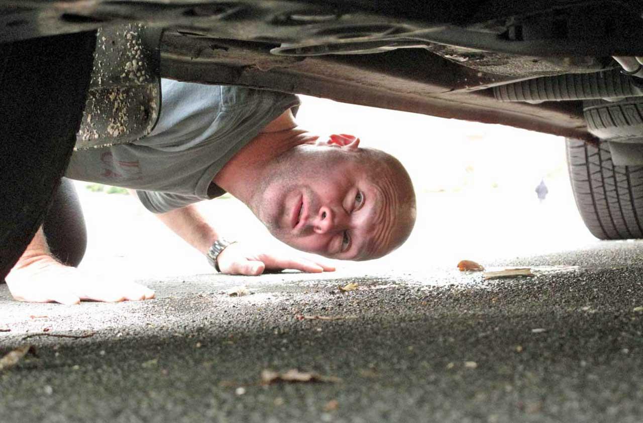 man checking out car