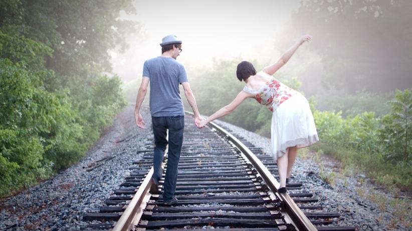 couple walking on train rails