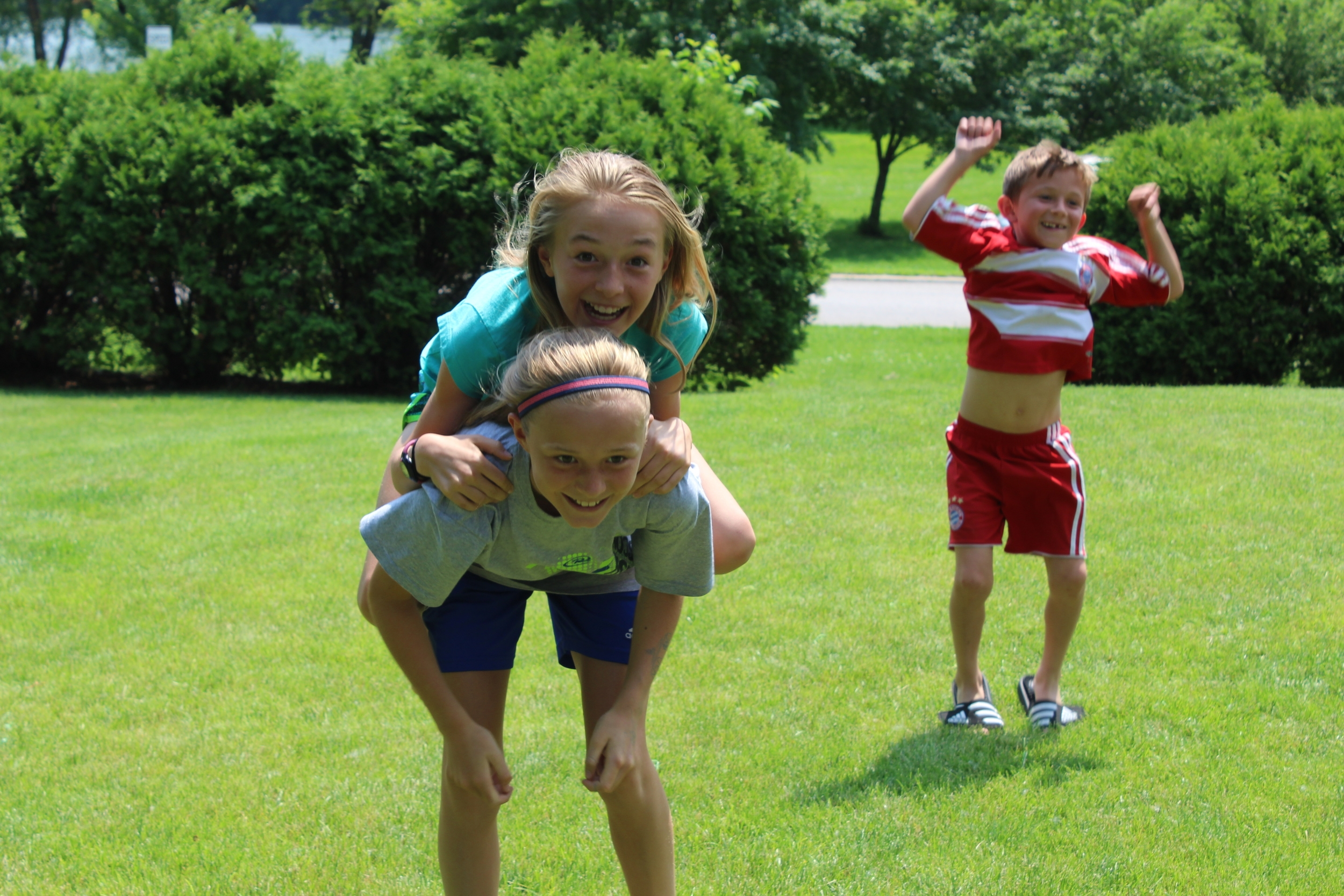 Lauren Ping gets a piggyback ride from her sister Lauren, while younger brother Jamison jumps in the background.