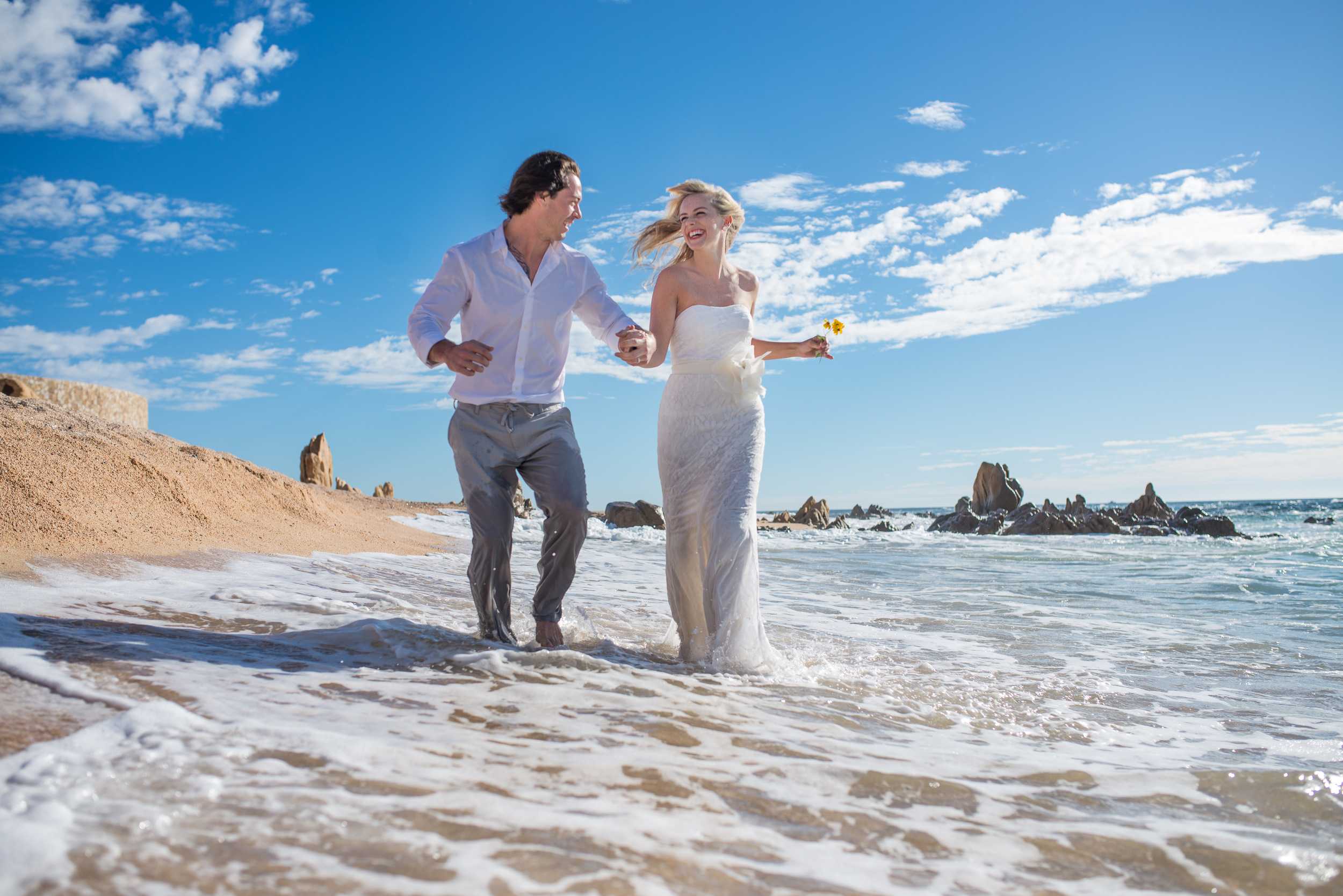 Bride and groom running and having fun on the sunny beaches of Cabo San Lucas