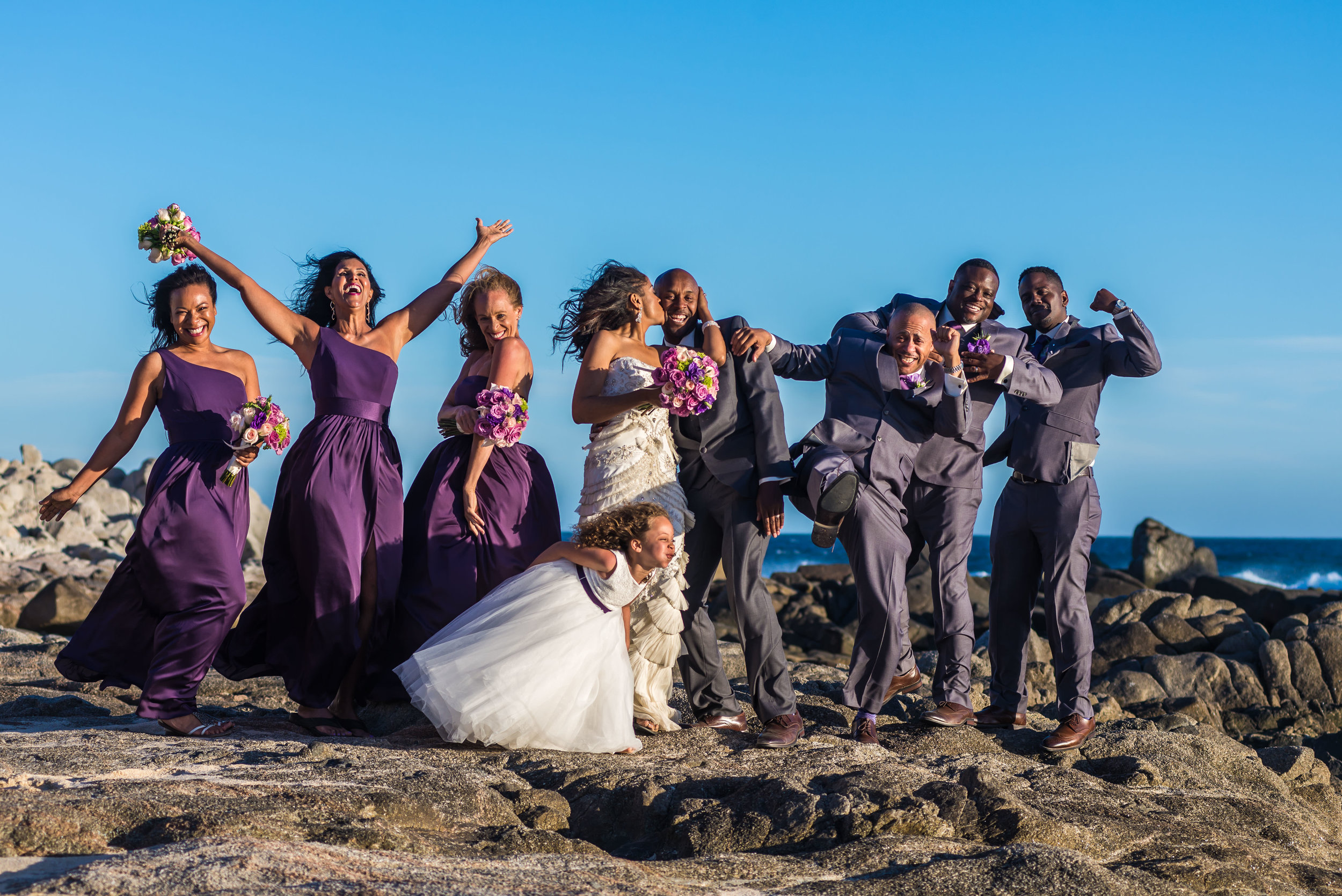 Bridal partyposing on the rocks during their photosession with talented GVphotographer