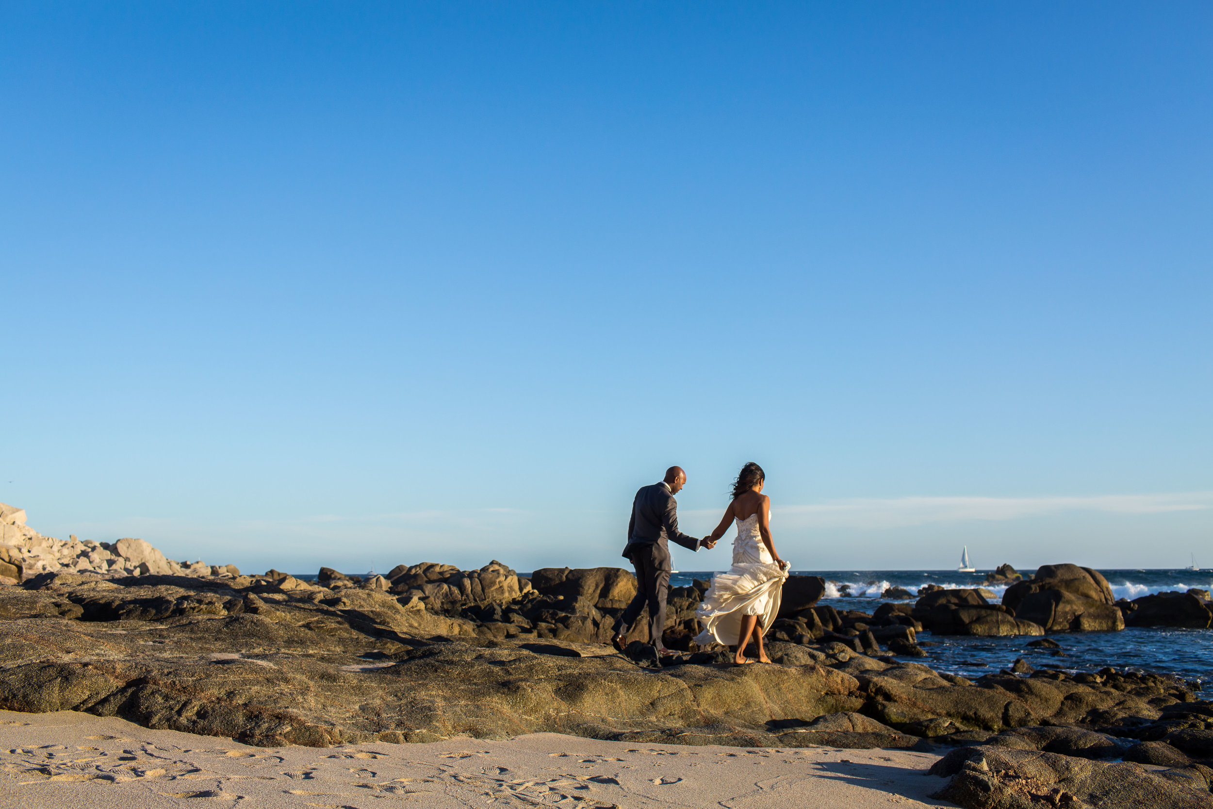 Bride and groom walking on the rocky beach of Cabo San Lucas during their photosession with local photographer