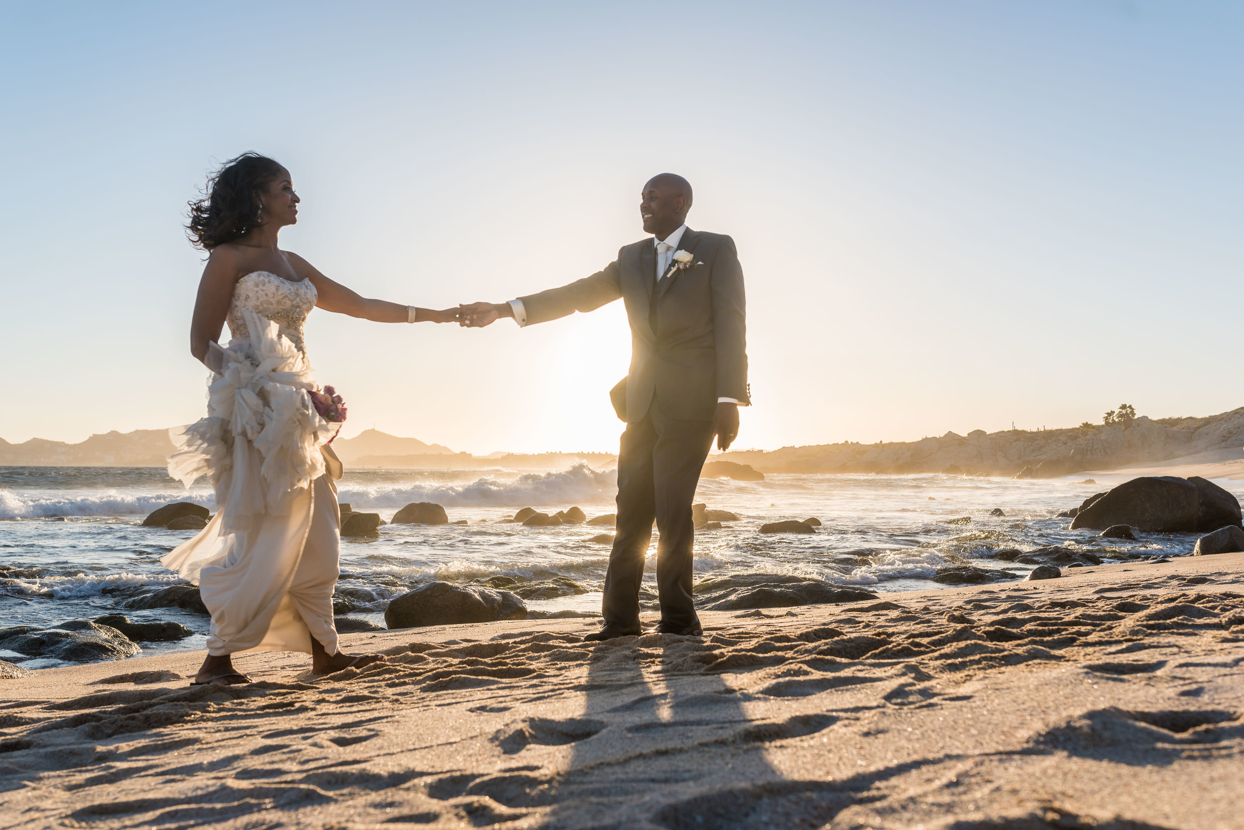 Bride and groom playing on the beach during their sunset photo session