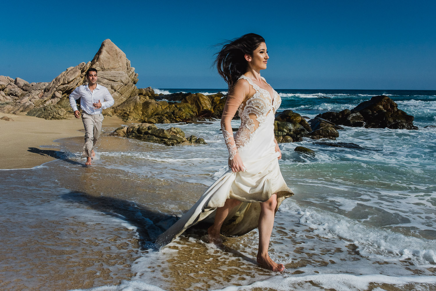 Running on the beach bride and groom during a trash the dress session at Sheraton Los Cabos