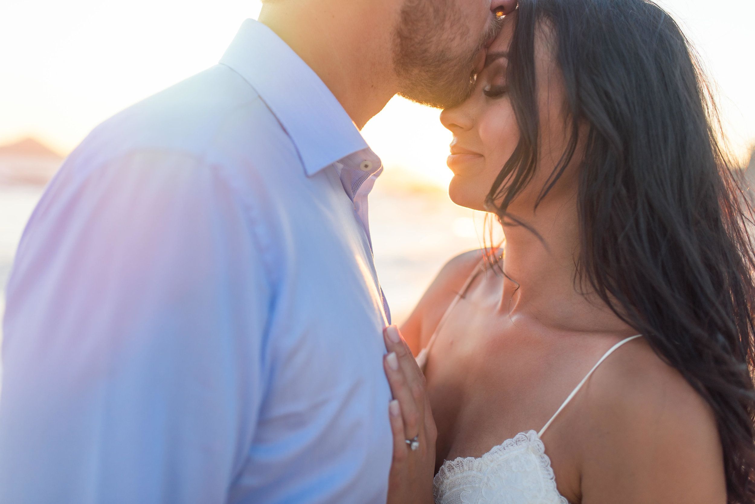 Couple kisses at the beach during the photo shooting with talented GVphotographer. Sunset is right behind them