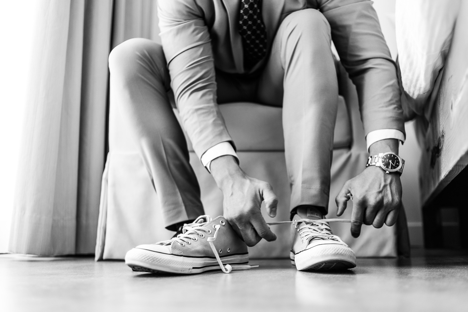 Groom is getting ready at his wedding day, Here you can see final touch of his Converse shoes. GVphotographer is professional destination wedding photographer based in Cabo San Lucas, Mexico