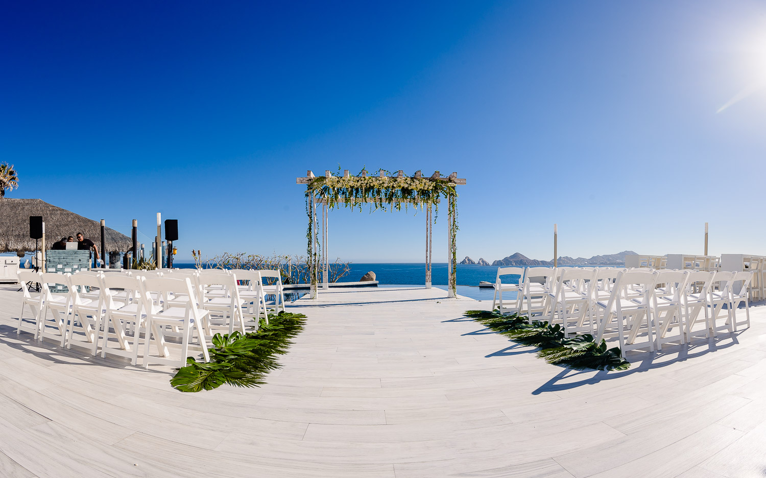 Sunset Monalisa wedding set up. Ocean view, wedding hopa and white chairs