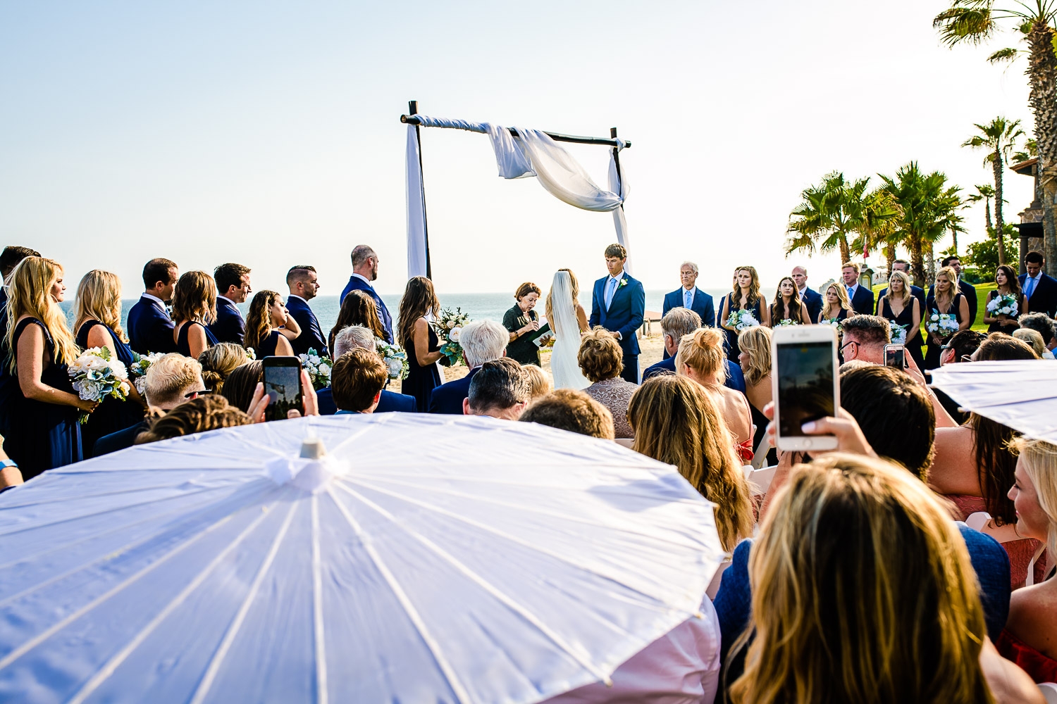 Bride and groom looking at each other during their destination wedding ceremony. Ocean is behind and they are surrounded with a lot of family and friends.