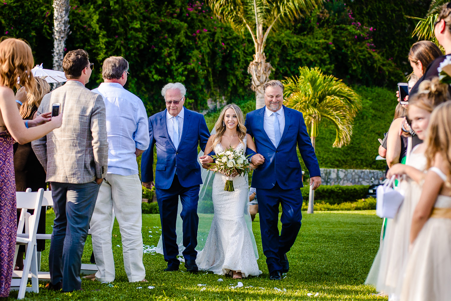 The bride is looking fabulous in her white gown and is smiling while walking in the beautiful garden Pueblo Bonito Sunset. GVphotographer is an amazing destination wedding photographer based in Cabo San Lucas, Mexico