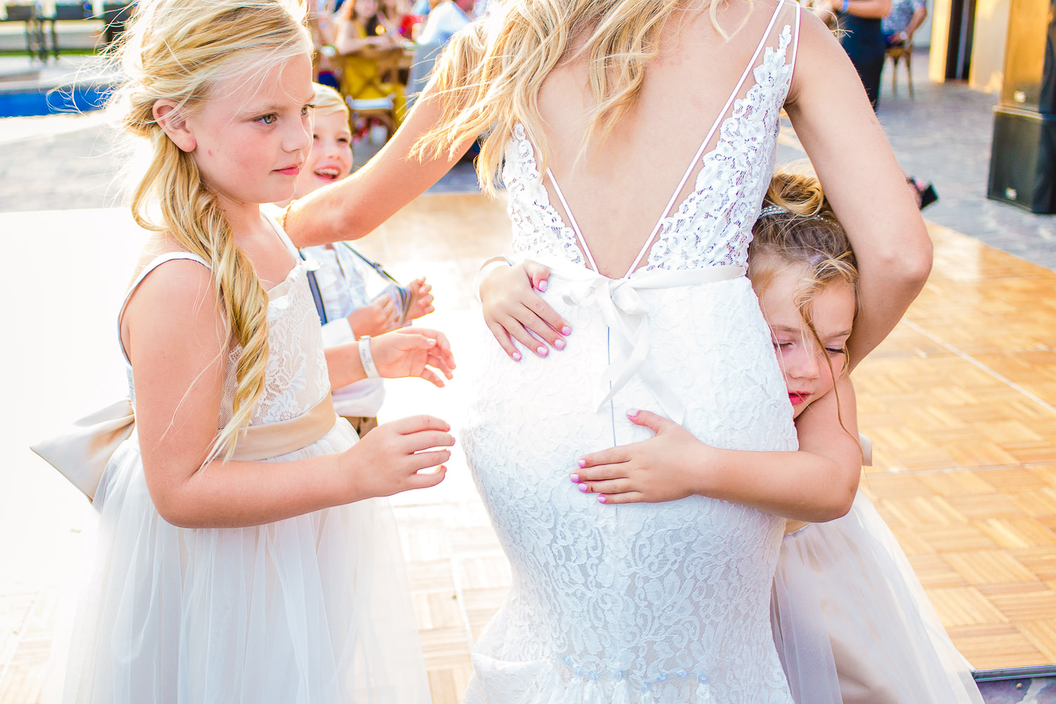 Two lovely kids are hugging the stunning bride dressed in white gown. GVphotographer is an amazing Los Cabos, Mexico destination wedding professional photographer