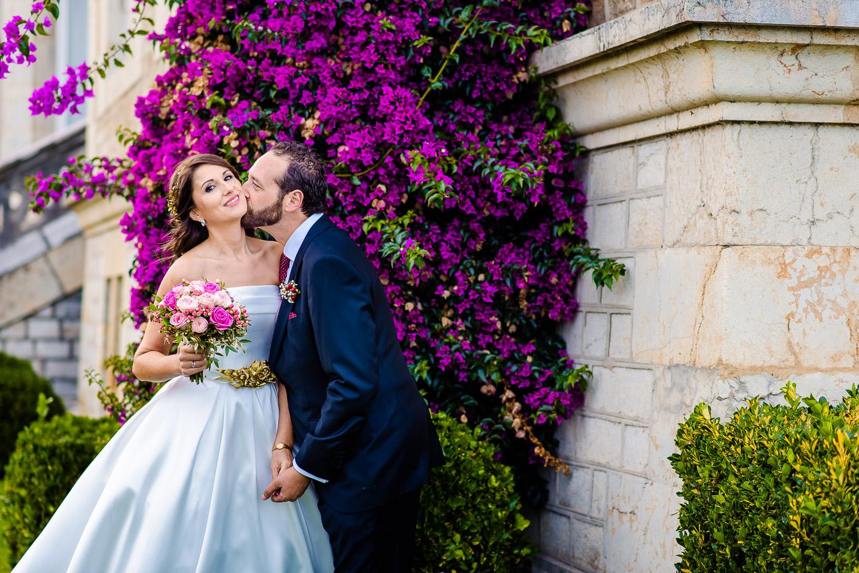 Bride and groom kising, with beautiful flowers behind them at el Palacio de la Magdalena
