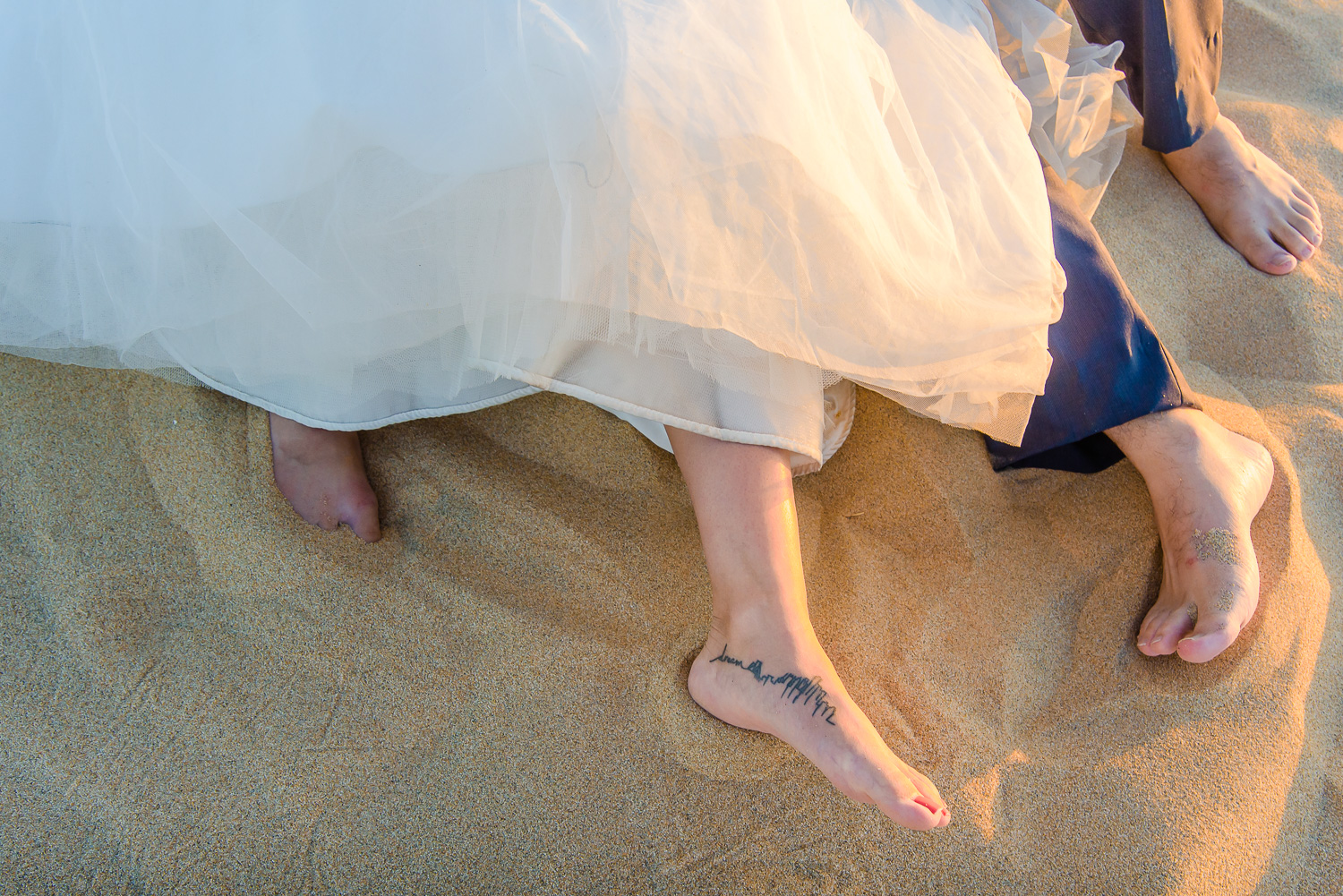 Bride and groom trash teh dress, both of them are layng down on the sand and barefoot. Bride has an interesting tatoo on her leg
