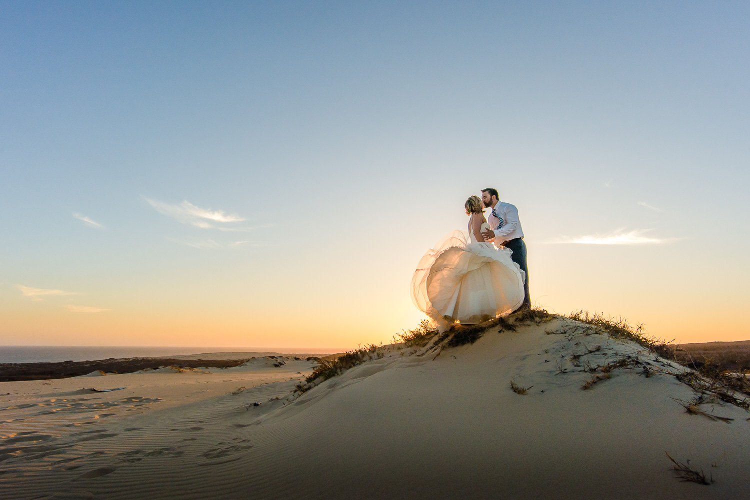 Bride and Groom kissing on top of a small dune during an amazing sunset in Cabo San Lucas