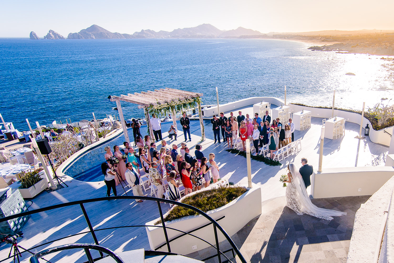 Aerial photo during a Los Cabos  wedding ceremony. Bride and father of the bride walking to the aisle. Blue ocean and famouse cabo arch as a background