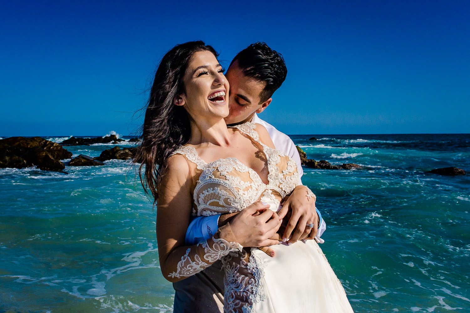 Bride and groom during her trash the dress session in Los Cabos. Both of them are laughing as the groom is holding his beautiful bride from behind on the beach