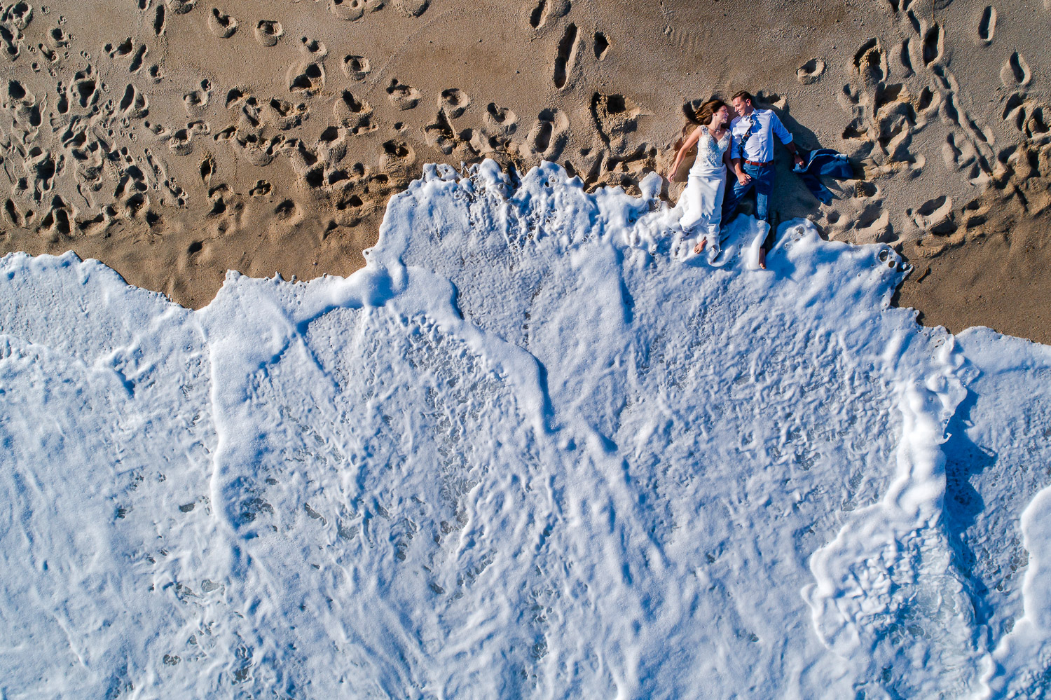 Aerial photo of bride and groom laying down on the beach during their trash the dress session with gvphotographer