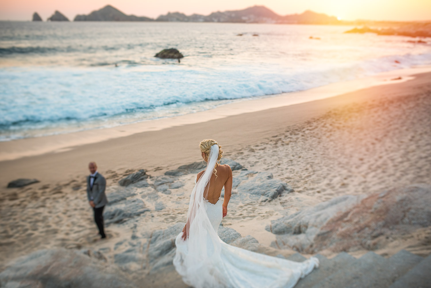 Gorgous bride standing on the rocks, grooms is behind on the beach and behind them is the ocean and the famous Cabo Arch of Cabo San Lucas