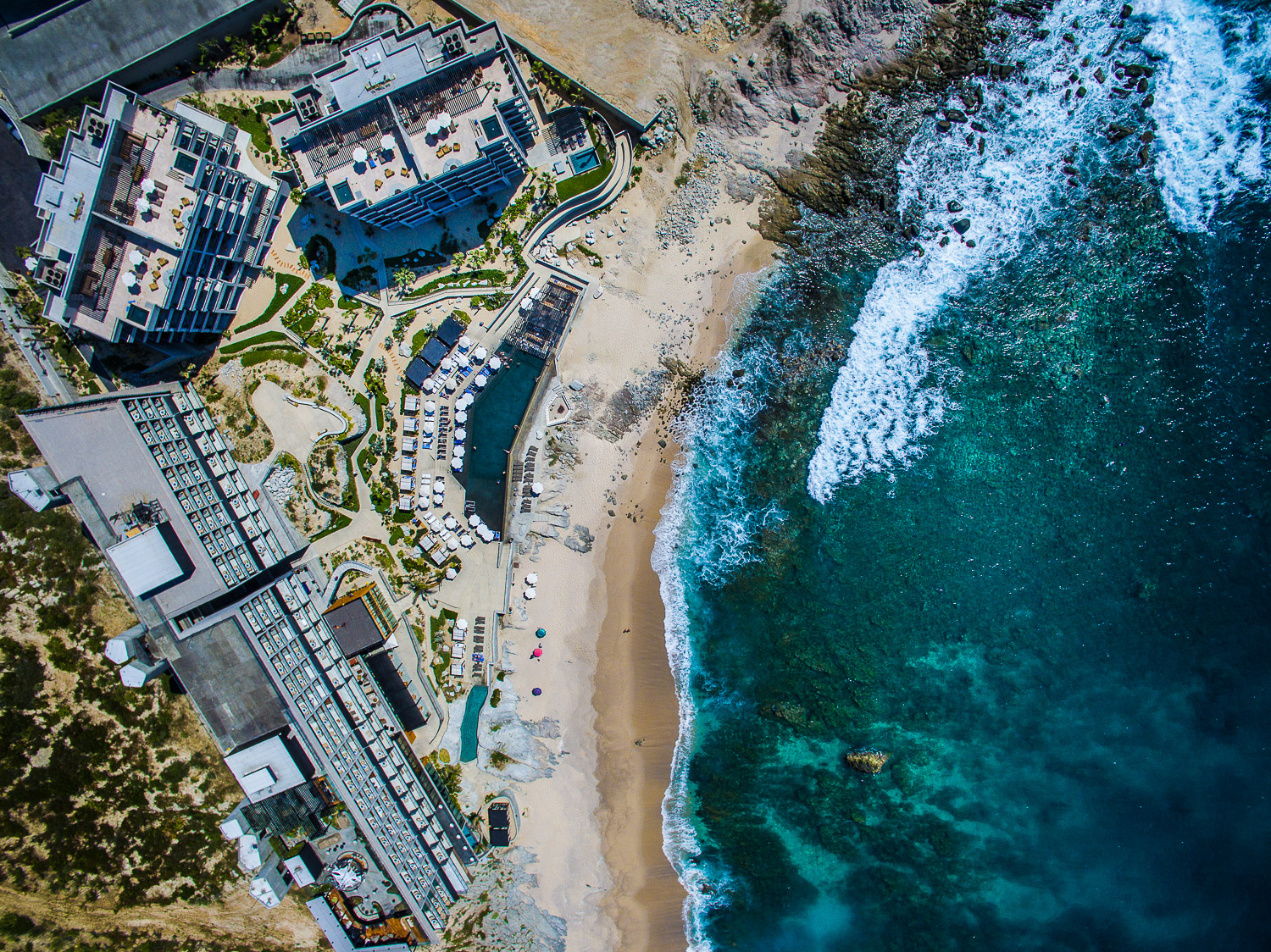 Aerial view of The Cape resort in Cabo San Lucas, Mexico. Four bildings, two pools, beach and the Sea of Cortez
