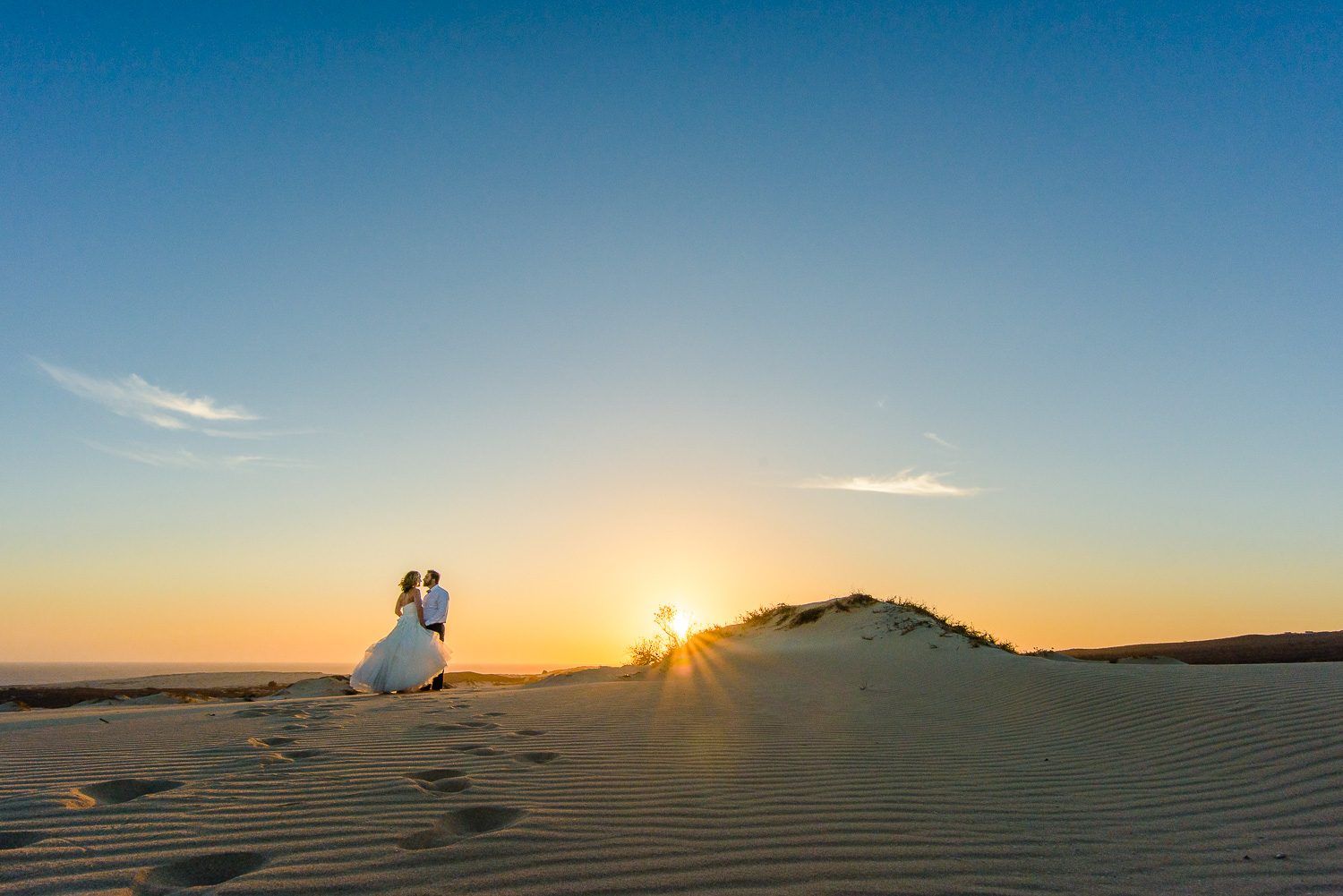 Bride and groom during their sunset photo session on their Cabo wedding. Kissing on the dunes with the sun behind. Photo by talented Cabo wedding photographer GVphotographer  https://www.gvphotographer.com/blog/creating-the-perfect-timeline-for-your-cabo-destination-wedding