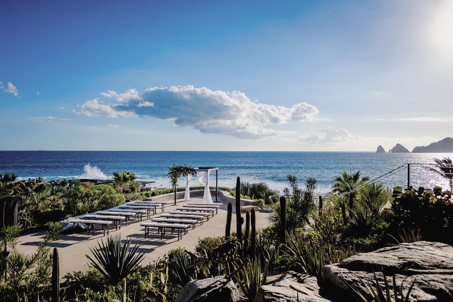 Simple wooden ceremony canopy. Framed by soft gauzy drapes billowing in the breeze and a romantic display of lush white garden roses. Simple adornment for an already spectacular setting! Low upholstered wooden benches keep the Ocean view and the Arch Rock formation uninterrupted.