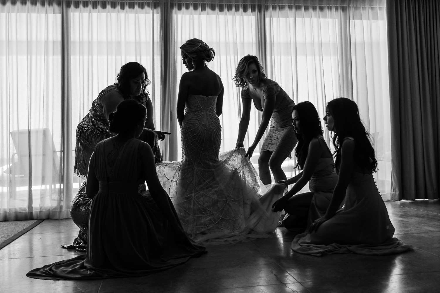 Bride is wearing her lovely white gown with intricate designing   The picture beautifully captures from back the bride getting ready on her wedding day. She is wearing an elegant white gown with intricate details on it and is getting it set with the help of five of her bridesmaids- destination wedding of the wonderful couple at the beautiful El Ganzo, Baja California Sur. GVphotographer is an amazing destination wedding photographer based in Cabo San Lucas, Mexico