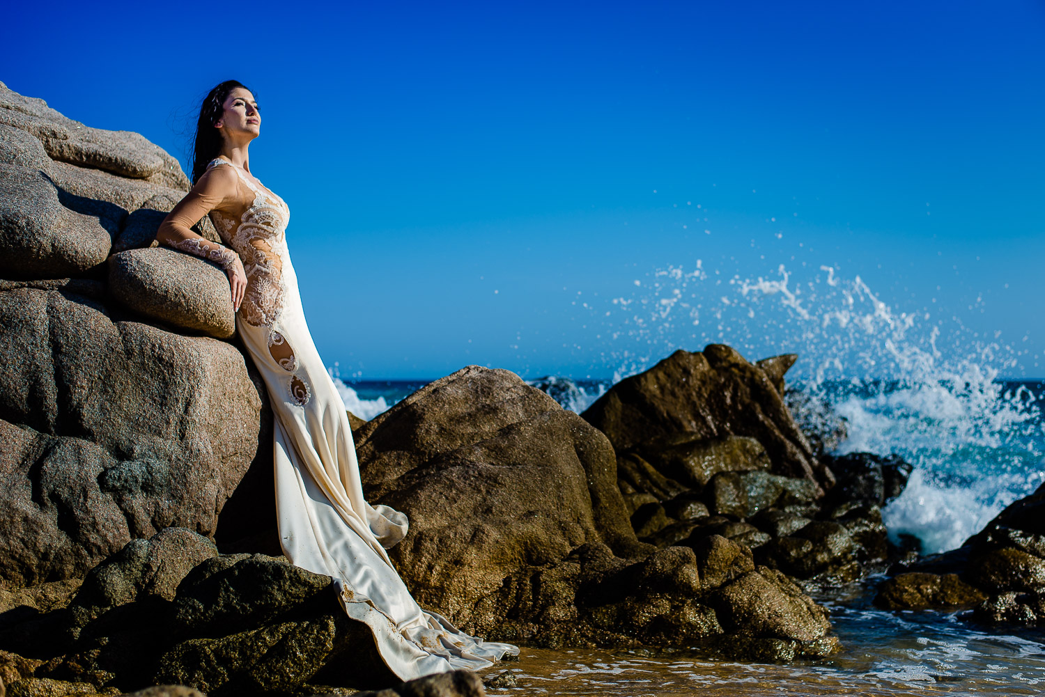Lovely bride is posing beautifully for the camera   Lovely bride is standing on on the rocks and infront of the beautiful blue beach. The bride is looking gorgeous posing for the camera under the bright sun and the rough water - destination wedding of the wonderful couple Hagop and Rose at the picturesque Sheraton Los Cabos on the beach. GVphotographer is an amazing destination wedding photographer based in Cabo San Lucas, Mexico