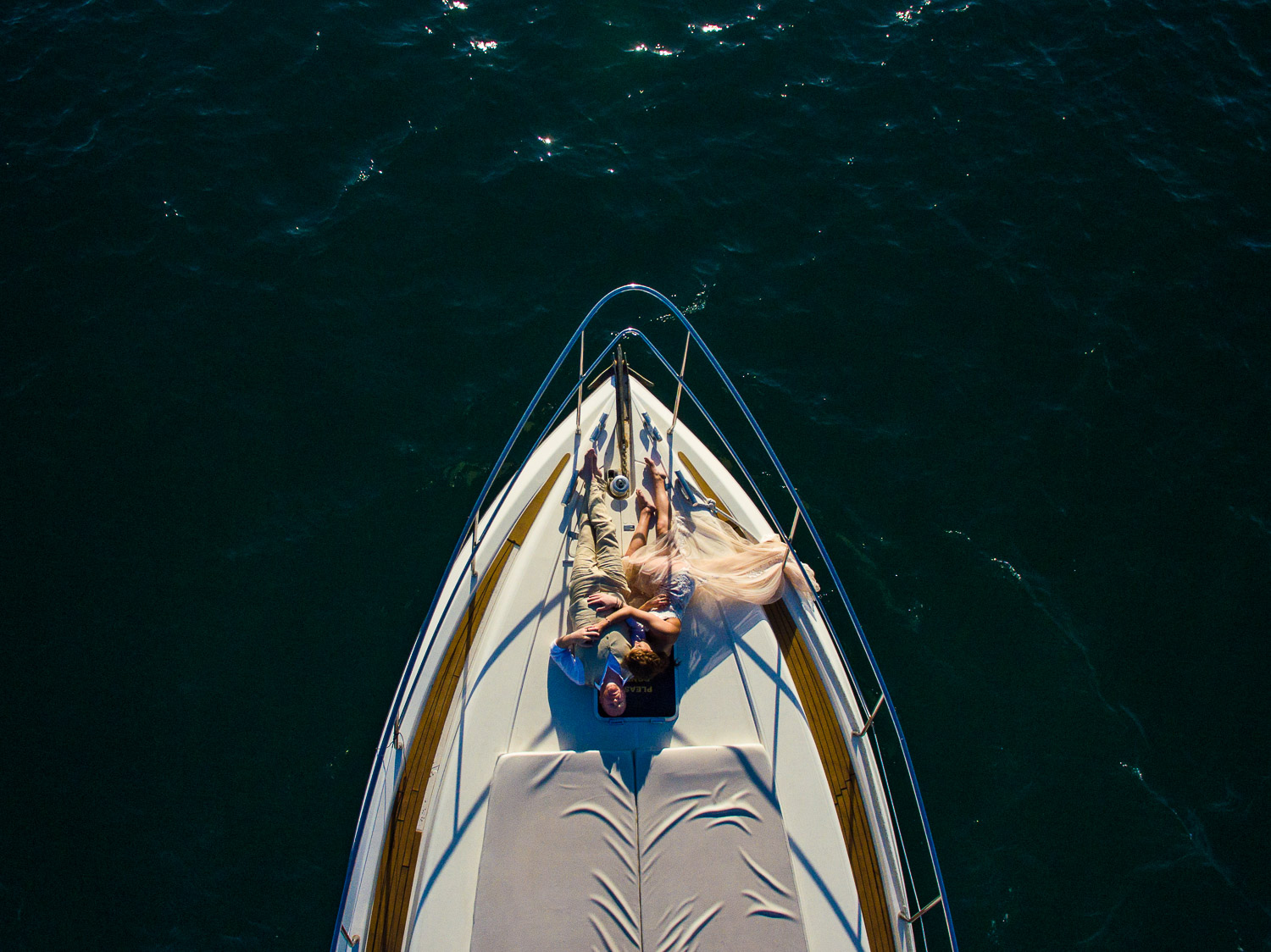 Bride and Groom on their wedding day are posing on a boat for an aerial drone picture by talented GVphotographer. GVphotographer is a destination Cabo Wedding photographer