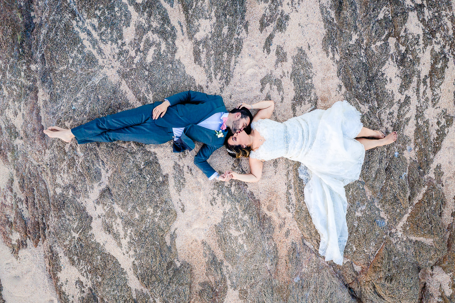 Aerial shoot of bride and groom kissing on the rocks during their wedding day at Fiesta Americana Los Cabos