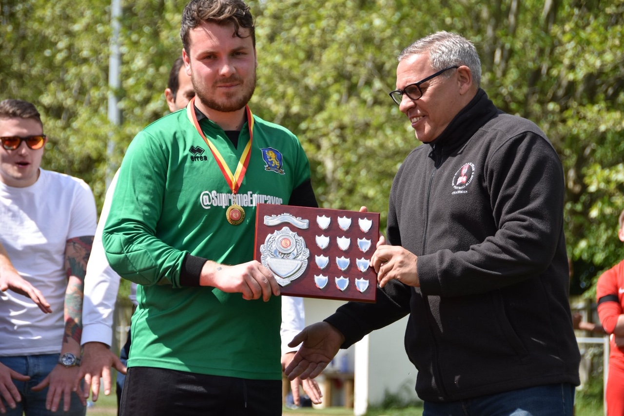 Vanbrugh's captain receives the WESFA Memorial Shield from League Chairman Dave Fone after saving a penalty in the shootout against Junior Reds Athletic to win the tie.