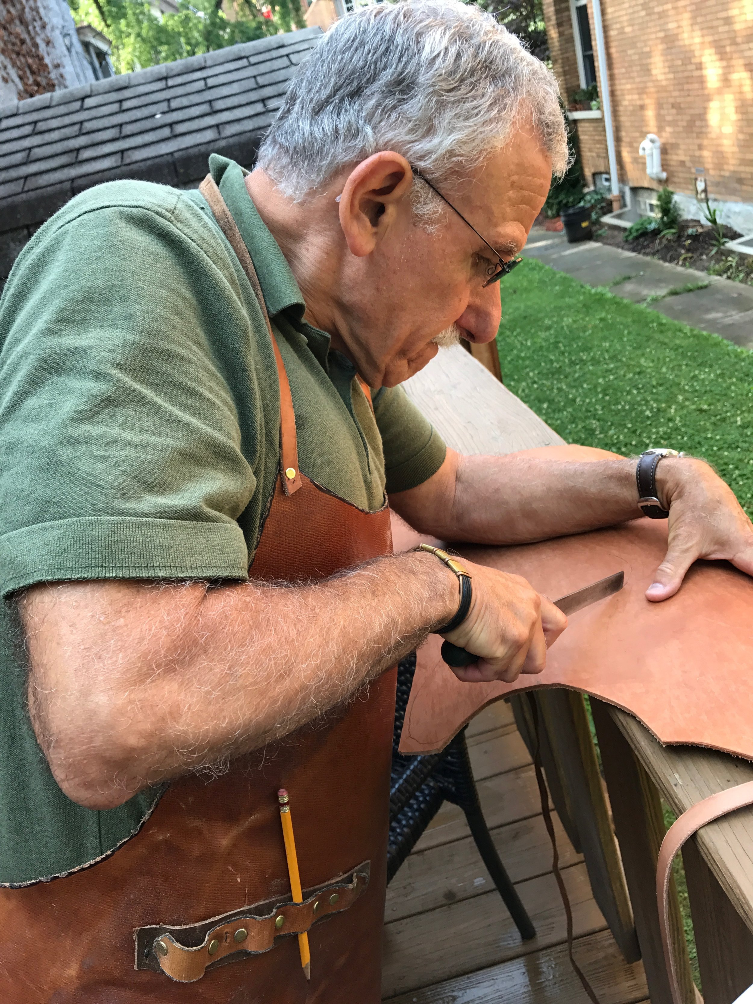 Eddie cutting out the soles of my sandals. That apron...